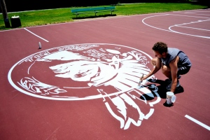 Adam Tracy puts the finishing touches on the Burr's Hill logo while working at the Warren park with the Hometown Revival Project. (Photo courtesy of East Bay Newspapers)